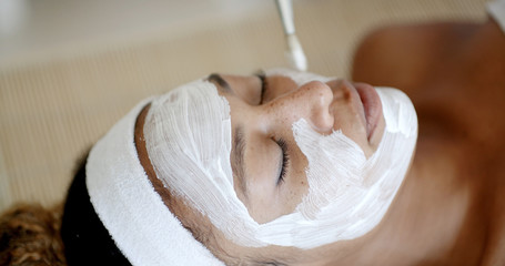 Cosmetician applying facial mask to the face of young woman in spa salon