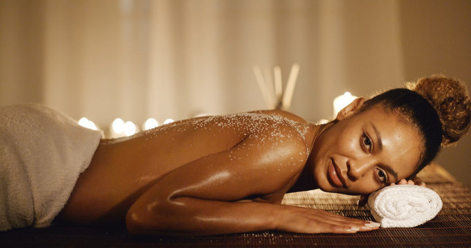 Smiling young woman lying on massage table with salt scrub on back in the health spa