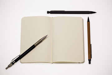 Open blank pages and pens on white background