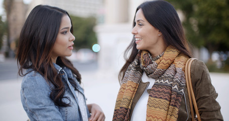 Two stylish smiling young women standing facing each other chatting outdoors in a town square  head and shoulders in winter fashion