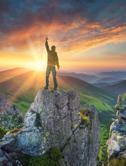 Silhouette of a champion on mountain peak. Active life concept.