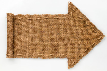 Arrow of burlap with curled edges lies on a white  background,