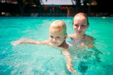 closeup mother small daughter swim smile in azure water of pool