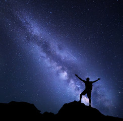 Milky Way. Night sky with stars and silhouette of a happy man with backpack and raised up arms. Space background