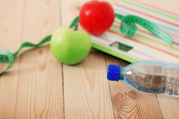 Scales, fruits, water on the wooden background