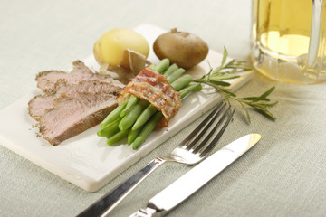 roasted lamb with beans in bacon and potatoes