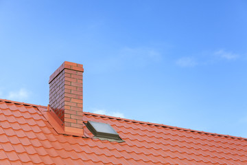 Roof with ceramic tile chimney against blue sky, space for text.