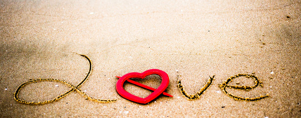 Red heart inthe sand.