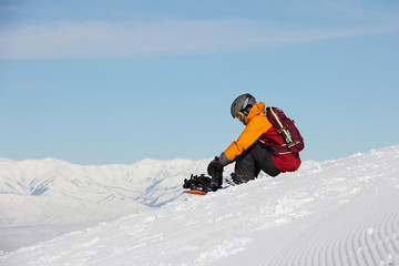 girl sitting on a slope and prepares a snowboard