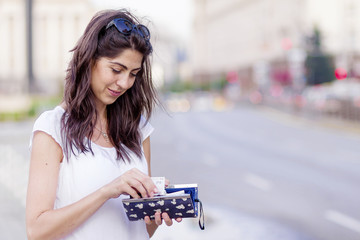 portrait of a beautiful smiling woman with wallet in the hands on the street.Saving money