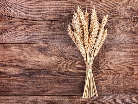 Ripe ears of wheat on old board