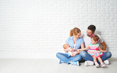 happy family father mother and children at empty wall