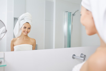 young woman coming out of the bathroom dressed in a white towel