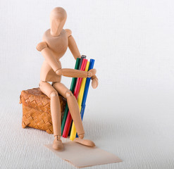 Wooden doll with colored felt-tip pen on a wicker casket.