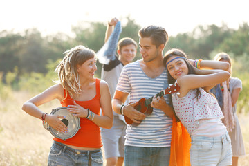 Carefree friends with guitar and drum, outdoors