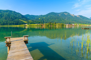 Wall Mural - Wooden pier and view of beautiful Weissensee lake in summer landscape of Alps Mountains, Austria