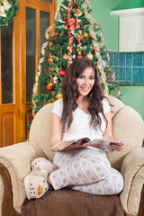 Pretty young woman reading magazine sitting on sofa smiling