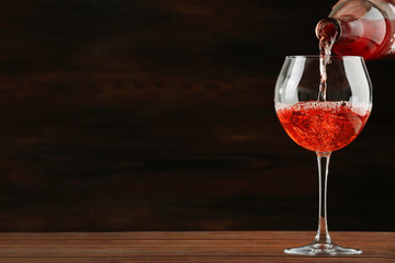 Rose wine pouring in glass on wooden background