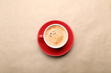 Cup of coffee on beige background, top view