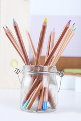 Set of coloured pencils in a glass pot on a table