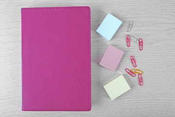 Coloured clips and stickers and notebook on white table