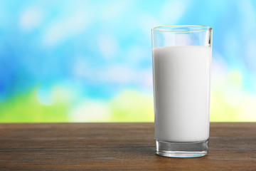 Glass of milk on table on blurred natural background
