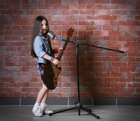 Beautiful little girl with microphone and guitar on brick wall background