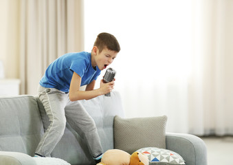 Little boy singing with microphone on a sofa at home
