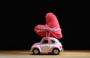 Miniature pink car carrying a red heart