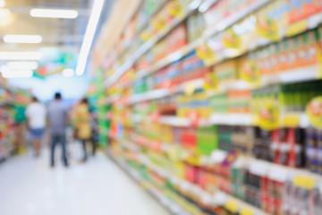Many different drink bottles on supermarket shelves blurred back