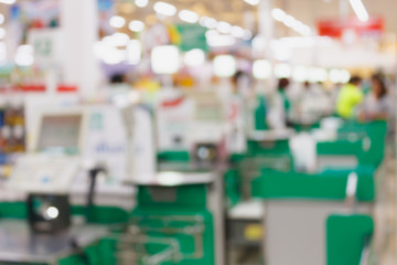 supermarket checkout payment terminal with customers blurred bac