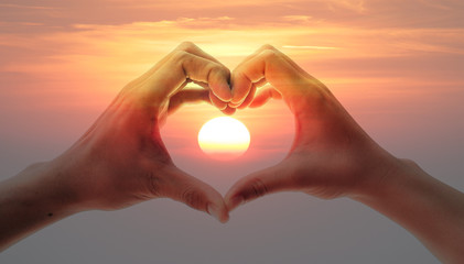 Lovers couple hands in Valentine' s heart with sunset background