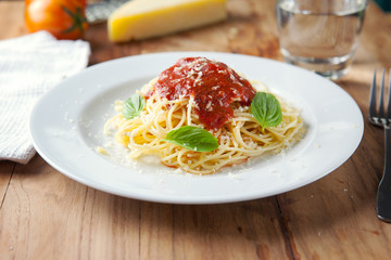 spaghetti with tomato sauce in plate on wooden board