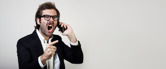 Portrait of young man wearing trendy suit and furiously screaming with smartphone. Wide