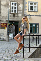 Blonde girl in hot pants sitting on a handrail