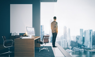 Businessman wearing modern suit and looking at the city in contemporary office.