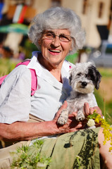 beautiful Senior smiling woman hugging her small white poodle dog in the mountain
