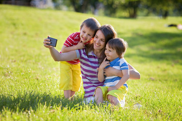 Happy mother with two kids, taking pictures in the park, outdoor