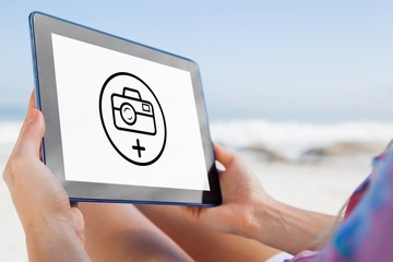 Woman sitting on beach in deck chair using tablet