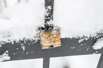 Liebesschloß mit Herzen am Zaun, verschneit - Nahaufnahme