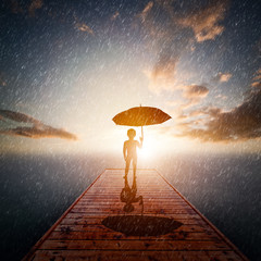 Child with umbrella standing alone wooden jetty in rain looking at the sea.