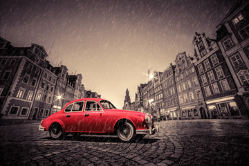 Wall Mural - Retro red car on cobblestone historic old town in rain. Wroclaw, Poland.