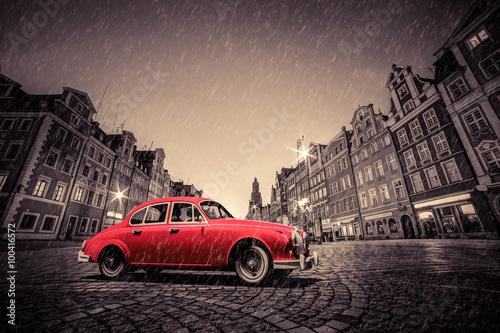 Fototapete Retro red car on cobblestone historic old town in rain. Wroclaw, Poland.