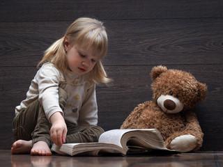 Маленькая девочка читает книгу. У девочки две косички, ребенок в джинсах и босиком. Рядом сидит игрушка медвежонок.