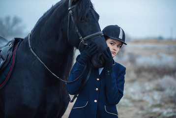 a tall girl with long blond hair in a jockey outfit with a beautiful black horse in an empty snow-covered field in winter