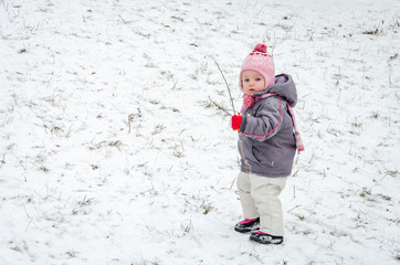 Little baby girl beautiful winter day playing in the snow wearing a jacket hooded down jacket, trousers, hat and gloves