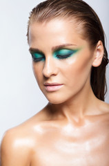 Portrait of young beautiful woman with green wet shining makeup