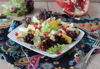 salad with quail eggs, cheese, pomegranate, orange