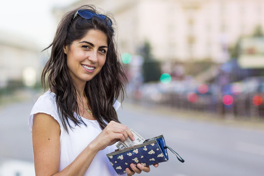 portrait of a beautiful smiling woman with wallet in the hands on the street.saving money concept