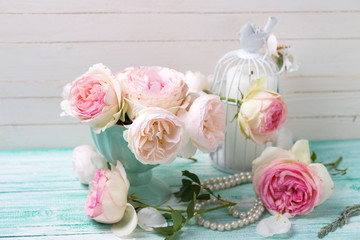 Pink roses and candle on turquoise painted wooden planks